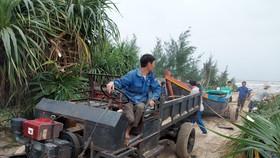 Sáng 25-10, ngư dân ở thị trấn Thiên Cẩm (huyện Cẩm Xuyên, Hà Tĩnh) kéo tàu lên bờ tránh bão