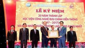 Phó Thủ tướng Vũ Đức Đam trao tặng Huân chương Lao động hạng Nhất của Chủ tịch nước cho Học viện Công nghệ Bưu chính Viễn thông. Ảnh: TTXVN