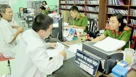 Nữ cảnh sát trẻ Nguyễn Thị Ngọc Diệp hướng dẫn người dân thủ tục nhập hộ khẩu