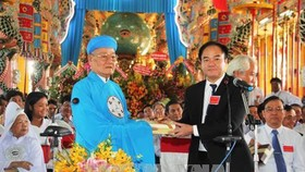 Đầu sư Thượng tám Thanh, Chưởng quản Hội thánh cao Đài Tây Ninh nhận quà chúc mừng của Ban Tôn giáo Chính phủ. Ảnh: TTXVN