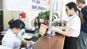 Việc sắp xếp lại bộ máy nhằm thực hiện mục tiêu tinh giản biên chế, nâng cao hiệu lực, hiệu quả điều hành và phục vụ người dân tốt hơn. (Trong ảnh: Người dân đang làm thủ tục ở huyện Nhà Bè)