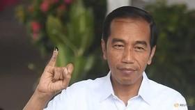 Tổng thống Indonesia Joko Widodo giơ ngón tay in mực sau khi bỏ phiếu tại thủ đô Jakarta. Ảnh: REUTERS