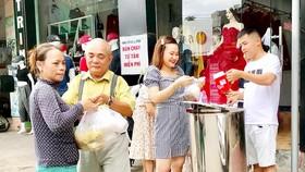 Một phụ nữ nghèo (bìa trái) nhận suất ăn sáng cho cả nhà từ nhóm bạn anh Huỳnh Nghĩa