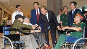 Thủ tướng thăm hỏi các đồng chí thương binh nặng tới dự buổi gặp mặt. Ảnh: VGP