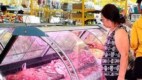 Người tiêu dùng tần ngần trước quầy thịt heo vì giá tăng cao. Ảnh: BÙI ANH TUẤN