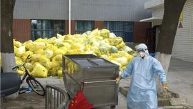 Một công nhân vệ sinh xử lý rác thải y tế tại một bệnh viện ở Thành phố Vũ Hán, Trung Quốc. Ảnh: XINHUA