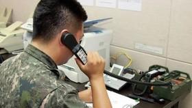 Bộ Thống nhất Hàn Quốc cho biết, đến trưa 9-6, việc liên lạc qua điện thoại với Triều Tiên đã không thể thực hiện được. Trong ảnh: Một sĩ quan Quân đội Hàn Quốc đang sử dụng đường dây nóng quân sự để liên lạc với Triều Tiên. Ảnh: YONHAP