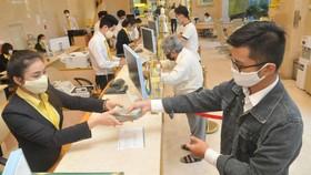 Giao dịch tại một ngân hàng ở TPHCM. Ảnh: CAO THĂNG