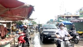 Cảnh nhộn nhịp mua bán, đi lại giữa công trường đang thi công nâng cấp mở rộng đường