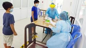 Nhân viên y tế quận Tân Bình, TPHCM lấy mẫu xét nghiệm cho người dân về từ Đà Nẵng