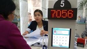 Giấy tờ được số hóa khi làm thủ tục  tại UBND quận 1. Ảnh: HOÀNG HÙNG