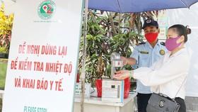 Nhân viên bảo vệ Trung tâm Y tế Thảo Điền, quận 2, TPHCM hướng dẫn người dân  sát khuẩn trước khi vào trung tâm. Ảnh: HOÀNG HÙNG