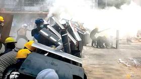 Người biểu tình ở Yangon che chắn đạn khói bằng các tấm khiên.  Ảnh: REUTERS