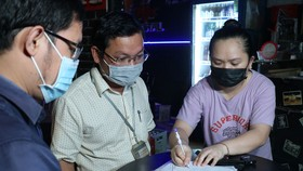 Đoàn kiểm tra quận Bình Thạnh nhắc nhở, tuyên truyền, buộc cơ sở kinh doanh  ký cam kết không  vi phạm tiếng ồn. Ảnh: THÁI PHƯƠNG
