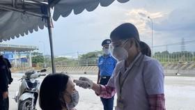 Kiểm tra thân nhiệt cho người đi đường tại chốt kiểm soát dịch trên Quốc lộ 1K phường Hóa An, TP Biên Hòa