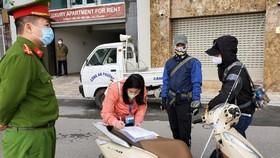 Lực lượng chức năng lập biên bản xử phạt hành chính một người đi ra đường có lý do không cần thiết giữa mùa dịch Covid-19