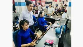 Ông Đỗ Quang Văn (đứng) kiểm tra hệ thống bán vé tại quầy vé ở Ga Sài Gòn. Ảnh: T.BA