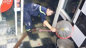 Lực lượng Cảnh sát PCCC và CNCH - CATPHCM hút nước đồng thời vớt rác tại các điểm úng ngập trong nhà dân