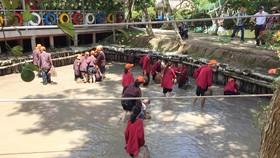 Khách du lịch trải nghiệm việc lội bùn bắt cá