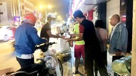 Các tình nguyện viên phân phát cháo cho người lao động  và người vô gia cư