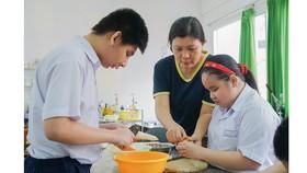 Cô Nguyễn Thị Kim Phượng hướng dẫn học trò những kỹ năng  hàng ngày, giúp các em hòa nhập với cuộc sống. Ảnh: HOÀNG HÙNG