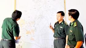 Đại tá Phan Minh Huyền (giữa), Bộ đội Biên phòng tỉnh An Giang, trao đổi về công tác phòng chống tội phạm trên bản đồ biên giới