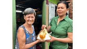 Chị Huỳnh Thị Phẩm mang bữa ăn đến tận nhà cho bà Lê Thị Mai