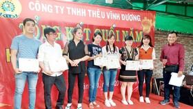 Anh Liêu Ngọc Sơn (bìa phải), Bí thư Chi bộ, Chủ tịch Công đoàn Công ty TNHH thêu Vĩnh Dương (quận Tân Phú, TPHCM) trao giấy khen cho đoàn viên có thành tích tốt trong sản xuất