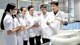 TS Nguyễn Hoàng Chinh đang hướng dẫn các sinh viên  tại phòng thí nghiệm Trường ĐH Tôn Đức Thắng