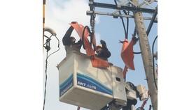 Nhân viên Tổng công ty Điện lực TPHCM đang sửa chữa  trên đường dây đang mang điện
