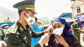 Các chiến sĩ Đồn Biên phòng Y Tý phát và hướng dẫn  đồng bào các dân tộc đeo khẩu trang, phòng dịch Covid-19. Ảnh: ĐBP