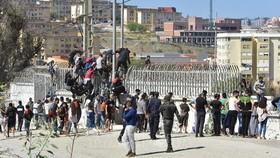 Người di cư trèo qua hàng rào biên giới tại Fnideq, Maroc, để sang vùng Ceuta của Tây Ban Nha ngày 18-5-2021. Ảnh: THX