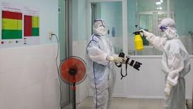Phóng viên  Báo SGGP thực hiện nghiêm túc và đầy đủ việc khử trùng để vào Bệnh viện Huyện Củ Chi tác nghiệp. Ảnh: DŨNG PHƯƠNG