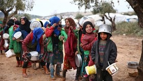 Trẻ em xếp hàng nhận thực phẩm cứu trợ tại một trại tị nạn ở tỉnh Aleppo, Syria