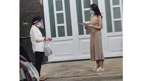 Bà Lê Thị Ngọc Bối (trái), Tổ trưởng Tổ 46 (khu phố 3,  phường 19, quận Bình Thạnh) đến nhà phát phiếu đăng ký  tiêm vaccine cho người dân