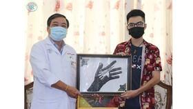 Anh Nguyễn Phước Quý Thành trao tặng tranh cho đại diện Bệnh viện Chợ Rẫy TPHCM.
