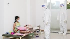 Nhân viên y tế thăm hỏi tình trạng sức khỏe của một trẻ mắc Covid-19. Ảnh: HOÀNG HÙNG
