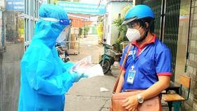 Anh Châu Tiến Lộc (phải), cán bộ Thành đoàn TPHCM,  cùng nhân viên y tế nắm tình hình F0 điều trị tại nhà
