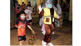 Các em thiếu nhi F0 đang cách ly tại Trường THCS Phạm Hữu Lầu (quận 7, TPHCM) tham gia rước đèn cùng chú Cuội, chị Hằng