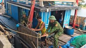 Bộ đội Biên phòng Hà Tĩnh giúp ngư dân chằng chống tàu  để tránh bão. Ảnh: DƯƠNG QUANG