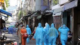 Nhân viên y tế thực hiện nhiệm vụ tại hẻm 287 Nguyễn Đình Chiểu, quận 3, nơi đang phong tỏa. Ảnh: DŨNG PHƯƠNG