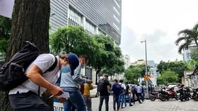 Hàng dài người dân dọc vỉa hè đường Hai Bà Trưng chờ nhận giấy đi đường vào khoảng 9h sáng 27-8. Ảnh: Ngọc Hiển.