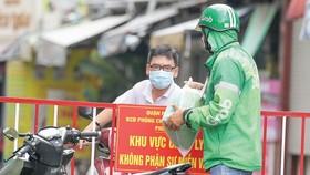 Shipper giao hàng cho khách trên đường Hoàng Văn Thụ, quận Phú Nhuận, TPHCM trưa 31-8. Ảnh: Hoàng Hùng.