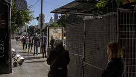 People line up a block away from Banco de la Nacion in Buenos Aires, Argentina, on April 3.  Photographer: Sarah Pabst/Bloomberg