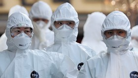 Medical workers in protective gear walk into a hospital facility to treat coronavirus patients in Daegu, South Korea, last month.   © Reuters