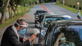 Kiểm tra thân nhiệt các tài xế nhằm ngăn chặn sự lây lan của dịch COVID-19 tại bang Parana, Brazil ngày 11/4/2020. Ảnh: AFP/TTXVN