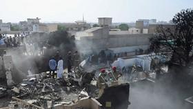 Hiện trường vụ rơi máy bay ở Karachi. (Ảnh: AFP/TTXVN)