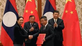 Ảnh minh họa - Chủ tịch lào Bounnhang Vorachith (phía sau bên trái) và Chủ tịch Trung Quốc Tập Cận Bình trong một ký kết hợp tác (Nguồn: cgtn)