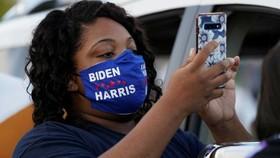 Một người ủng hộ Biden đang đọc tin nhắn văn bản. © Kevin Lamarque/Reuters