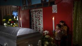 Hai con của nhà báo Julio Valdivia đứng bên cạnh quan tài ông quản tại nhà riêng ở Tezonapa, Veracruz, Mexico. Ảnh: AP